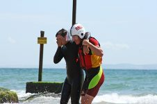 RNLI lifeguard helping ashore a casualty (putting arm around shoulder) during the One Big Rescue demonstration at Branksome Chine, Dorset.
