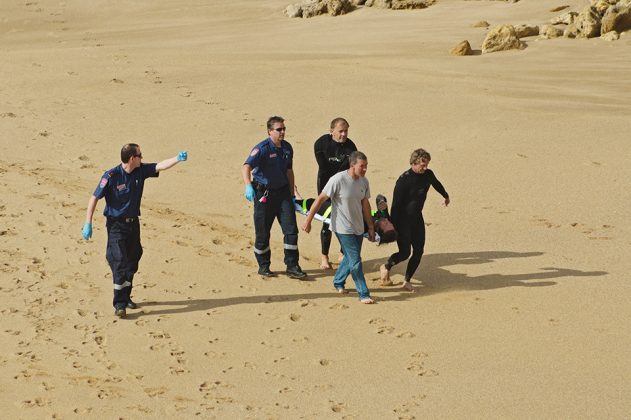 16895828 - paramedic in uniform points direction to group of surfers and another paramedic who carry injured surfer in a stretcher and walk on sand at bells beach, rocks in background, victoria, australia on december 15