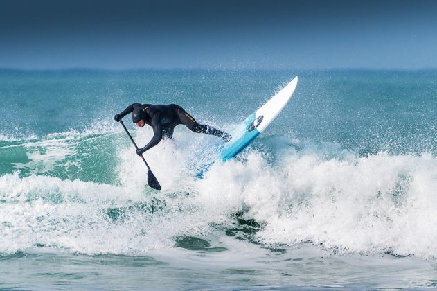 A paddle boarder riding a wave at Fistral in Newquay, Cornwall.