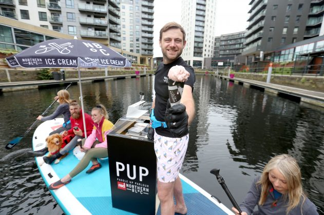 Picture : Lorne Campbell / Guzelian  Paddleboard enthusiasts  get an ice-cream from Josh Lee, co-founder of urban ice cream brand, Northern Bloc at the launch of the world's first paddle board ice-cream parlour, in Leeds, on Wednesday morning. Celebrating the start of National Ice Cream Month (1 July) the brand has teamed up with Red Paddle Co to seek the most carbon-friendly way to share its vegan ice creams whilst the sun shines.  Trialling the PUP (Paddle Up Parlour) on its home surf, Northern Bloc is trialling its parlour ahead of its next outing at Dogmasters, 2021, the UK dog surfing and SUP championships  PICTURE TAKEN ON WEDNESDAY 30 JUNE 2021.    FULL PRESS RELEASE BELOW  Ice Cream Float: worldÕs first paddleboard ice cream parlour makes maiden voyage for start of National Ice Cream Month  Vegan ice cream brand trials sustainable summer vehicle on Leeds canal ahead of summer celebrations  Paddleboard enthusiasts from Leeds, Jamie Crowther and Zoe Dawson, proved theyÕve got paddleboarding licked when they took to the water today to try out the worldÕs first paddleboard ice cream parlour, created by urban ice cream brand, Northern Bloc.    Celebrating the start of National Ice Cream Month (1 July) the brand has teamed up with Red Paddle Co to seek the most carbon-friendly way to share its vegan ice creams whilst the sun shines.   Trialling the PUP (Paddle Up Parlour) on its home surf, Northern Bloc is planning a schedule of pop-up paddleboard ice cream parlours as the UK basks in a staycation summer and the popularity of paddleboarding hits new heights.   The customised 17ft long XL Ride inflatable paddleboard ice cream parlour will take to the high seas in Bournemouth this month (25 July) for the UKÕs only Dog SUP Surfing Championships on Branksome Dene Chine beach. The internationally recognised event brings together lovers of dogs and the sea for a fun-packed day of surfing and paddleboarding competitions, as well as live music, food and drink.    Red Padd